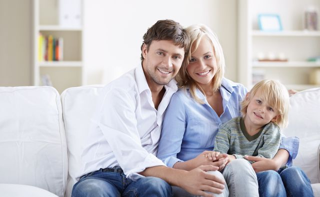 Young family with a child on the couch in the apartment